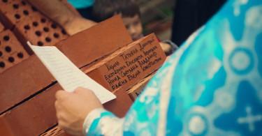 подписывают именные кирпичики строящегося храма во имя святителя Луки