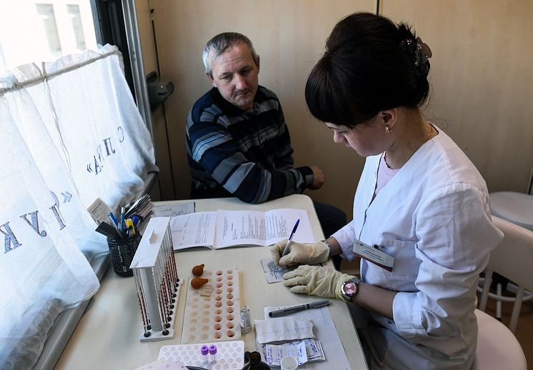 """KRASNOYARSK TERRITORY, RUSSIA - APRIL 16, 2018: A patient has a blood test at a medical centre named """"Doctor Voyno-Yasenetsky - Saint Luke"""" after surgeon and Orthodox archbishop Valentin Voyno-Yasenetsky (1877-1961), at Ingashskaya railway station as the centre travels by train across the Krasnoyarsk Territory and provides highly-qualified medical and diagnostic care to residents of its remote areas. Kirill Kukhmar/TASS Ðîññèÿ. Êðàñíîÿðñêèé êðàé. 18 àïðåëÿ 2018. Ïàöèåíò â ïðîöåäóðíîì êàáèíåòå ïåðåäâèæíîãî êîíñóëüòàòèâíî-äèàãíîñòè÷åñêîãî öåíòðà """"Äîêòîð Âîéíî-ßñåíåöêèé - Ñâÿòèòåëü Ëóêà"""" íà ñòàíöèè Èíãàøñêàÿ. Öåíòð îáåñïå÷èâàåò âûñîêîêâàëèôèöèðîâàííîé äèàãíîñòè÷åñêîé, êîíñóëüòàòèâíîé è ëå÷åáíîé ïîìîùüþ æèòåëåé â îòäàëåííûõ è òðóäíîäîñòóïíûõ ðàéîíàõ Êðàñíîÿðñêîãî êðàÿ. Êèðèëë Êóõìàðü/ÒÀÑÑ"""